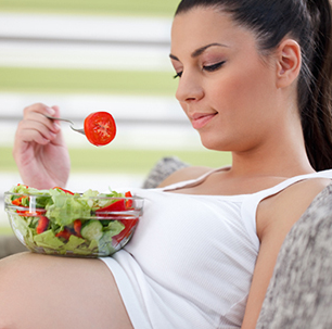 Беременная девушка ест салат